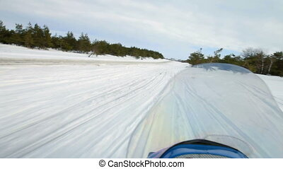 POV: winter recreational activity snowmobile riding in snowy mountains