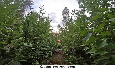 POV young boy rides a bicycle through the bush. Go pro ...