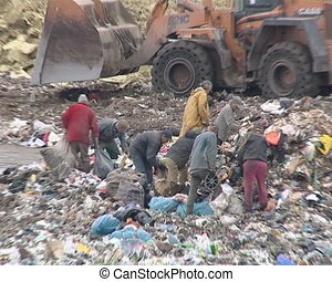 Poverty. Homeless between stacks of waste in dump looking for food and useful items. Environmental pollution.
