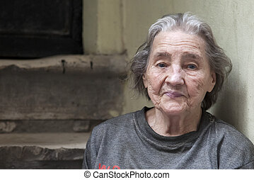 Old woman in poverty sitting on street