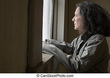 Poverty - Thirty-eight year old woman looking out the window...