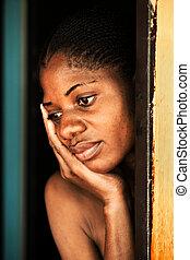 poverty - poor african woman in the door, village near...