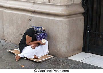 Barefoot poverty-stricken female beggar cowering down on an old piece of cardboard alonside a bulding with her face hidden and a begging cup in her hand