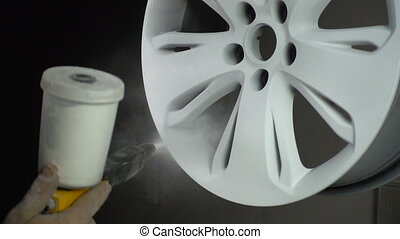Powder painting of auto disk, slow motion in workshop