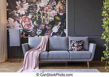Powder pink blanket thrown on grey couch in real photo of...
