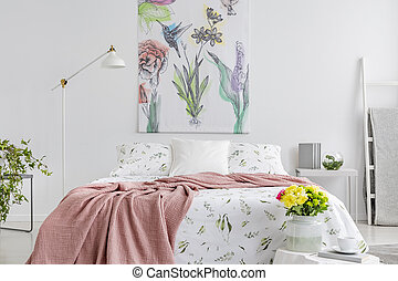 Powder pink blanket thrown on king-size bed with floral bedding in real photo of white bedroom interior with painting on the wall