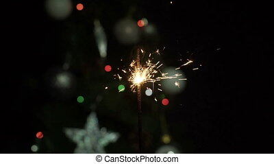 Powder sparks of Bengal lights against dark background with christmas tree. Slow Motion