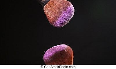 Powderbrush on black background with pink powder splash