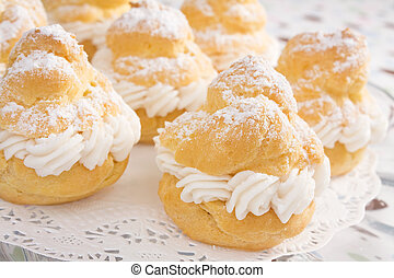 Cream puffs filled with pastry cream and sprinkled with powdered sugar.