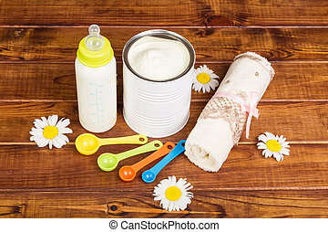 Powdered milk, with mixture bottle, measuring spoons on...