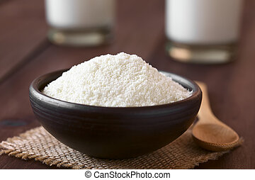 Powdered or dried milk in small bowl, photographed on dark wood with natural light (Selective Focus, Focus one third into the milk powder)