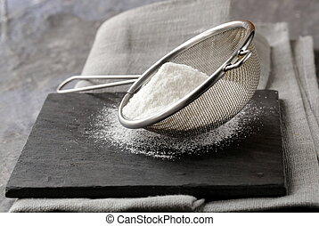 powdered sugar in a metal strainer on a gray background