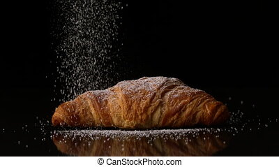 Powdered sugar sprinkling onto a croissant in slow motion