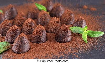 Powdering with cocoa chocolate truffles on slate closeup -...