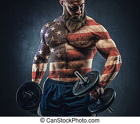 Power athletic bearded man in training pumping up muscles...