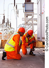 power company electrical co-workers in substation