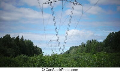 Power line support against the background of the blue sky with clouds are situated on the bank of the river in the summer wood