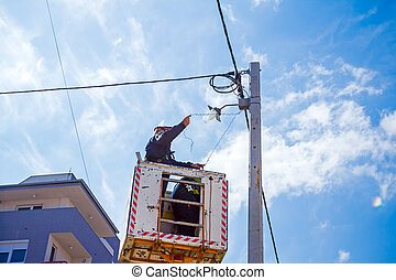 Power line team at work on a pole
