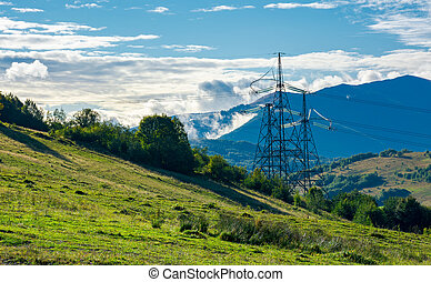 power line tower on the hill. huge mountain in clouds in the...