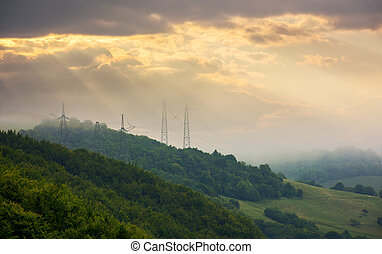 power line tower on the hill touch the cloud - foggy autumn...