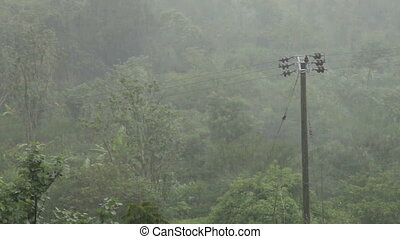 Power line under a heavy rain. Winter rainy season on Bali,...