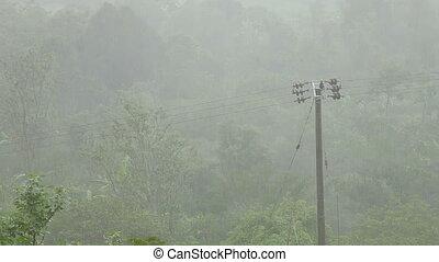 Power line under a heavy rain. Winter rainy season on Bali,...