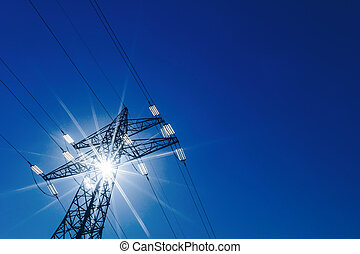 power line with sun - a high voltage power pylons against...