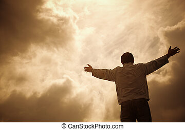 man and drammatic clouds, religion concept, selective focus