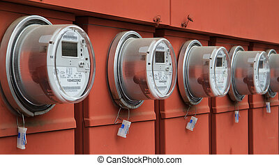 Power meters - Line up of five elecric power meters on red ...