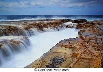Gallons of surging ocean waves overflow into a deep eroded rock ravine at Terrigal Haven NSW Australia