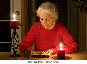 Power outage - Elderly lady sitting in candlelight reading...