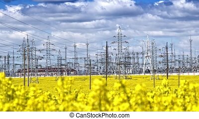 Power plant at the cloudy day and yellow rapeseed field at the foreground