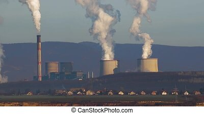 Power plant and village - Power plant cooling tower behind a...