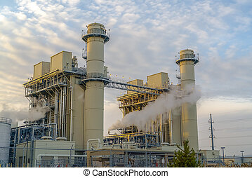 Power Plant releasing steam against pale blue sky with bright puffy clouds