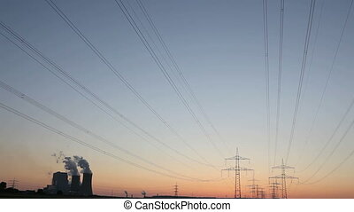 Power plant with power lines during sunset