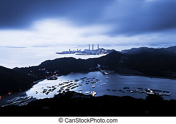 Power station at night with mountain landscape