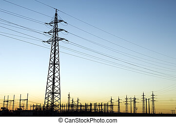 Power substation and pylon with distribution lines at sunset.