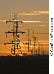 power sunset - Sun setting behind a row of electricity ...