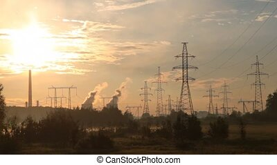 Power transmission lines poles stand against pipes of plant