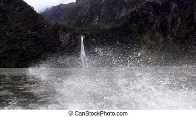 Power water of waterfall in a rocky coast and mountains New Zealand.