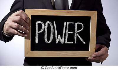 Power written on blackboard, businessman holding sign, business, politics