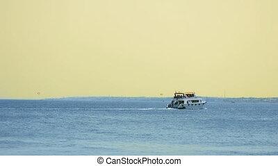 Powerboat ship sails at sunset along tropical sea -...