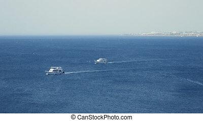 Powerboats and ship s sails along tropical sea - Powerboats...