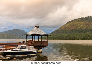 Powerboats at the pier with a gazebo and fog on Lake Teletskoye, Altai, Russia