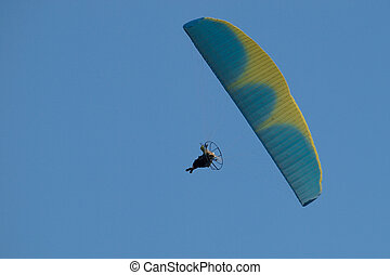 Powered paraglider pilot during the flight in blue sky