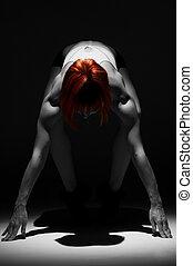 Powerful female athlete standing in the spotlight on black
