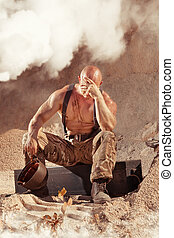 Powerful bald soldier in grief on the rocky background.