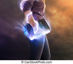 Powerful Bible. - A woman holds her Bible with glowing...