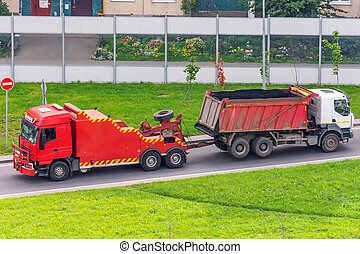 Powerful big rig semi truck tractor tows with attached broken evacuated bulk cargo truck driving on city highway.
