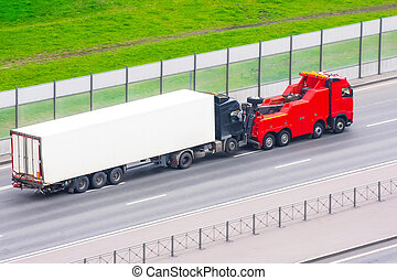 Powerful big rig semi truck tractor tows with attached broken evacuated truck with container trailer driving on city highway, aerial view.